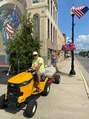 Harold and Marylyn Strang watering flower baskets in downtown Bucyrus.