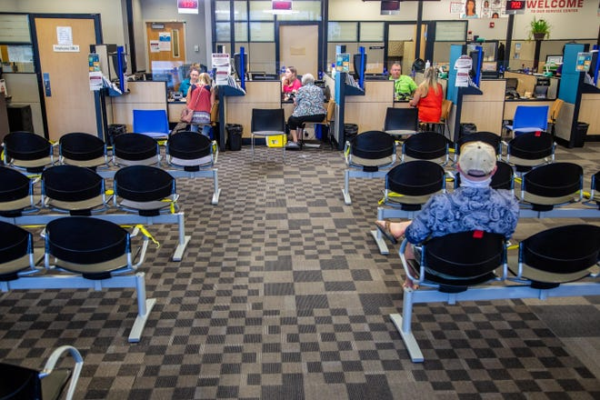 Caution tape blocks off seats and a red strip indicates an open seat to provide for social distancing at the Iowa DOT facility in Ankeny on July 29.