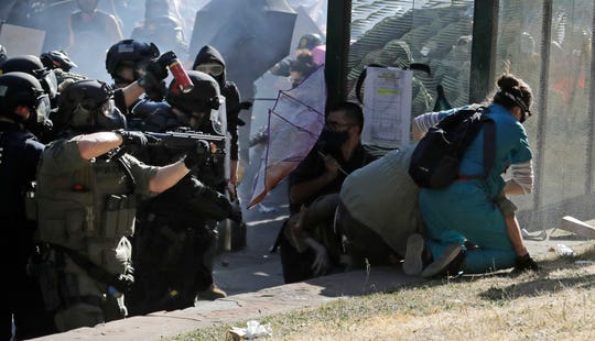 A nurse, right, who was providing volunteer medical care to protesters, comes to the aid of a person who was knocked down by police, as police take aim with a pepper-spray bottle and a rifle that fires less-lethal projectiles, Saturday, July 25, 2020, in Seattle as police clashed with protesters during a protest in support of Black Lives Matter and against police brutality and racial injustice at Seattle Central College in Seattle's Capitol Hill neighborhood.
