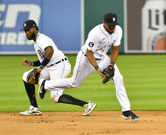 Tigers third baseman Jeimer Candelario runs and fields a ground ball in front of Niko Goodrum, left, and gets the out at first in the ninth inning against the Kansas City Royals on Tuesday.