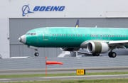 In this April 10, 2019, file photo a Boeing 737 MAX 8 airplane being built for India-based Jet Airways lands following a test flight at Boeing Field in Seattle.  Boeing says it lost $2.40 billion in the second quarter, and it's taking a more downbeat view about the airplane market because of the coronavirus outbreak.