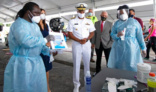 Vice Admiral Jerome Adams, the U.S. Surgeon General, speaks with health workers Gabriel Appoh, left, and Varaiaia Barkus at the COVID-19 drive-thru testing center at Miami-Dade County Auditorium in Miami on Thursday, July 23, 2020.