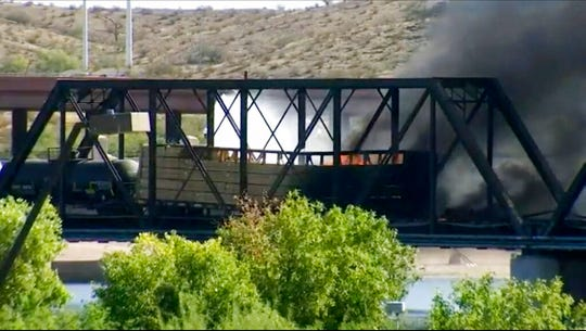 Smoke fills the sky at the scene of a train derailment in Tempe, Ariz., on Wednesday, July 29, 2020. Officials say a freight train traveling on a bridge that spans a lake in the Phoenix suburb derailed and set the bridge ablaze and partially collapsing the structure.  There were no immediate reports of any leaks.