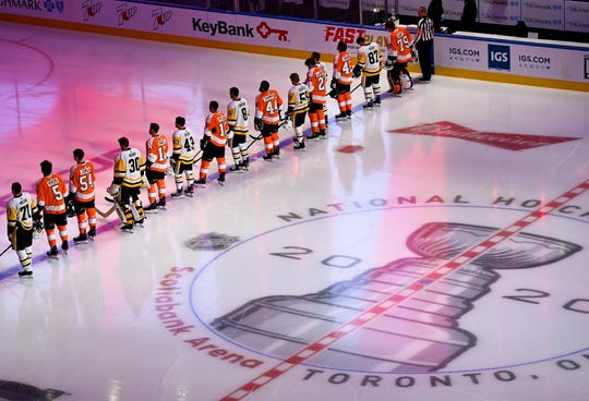 The Pittsburgh Penguins and Philadelphia Flyers line up together for the national anthems before an exhibition game Tuesday in Toronto.