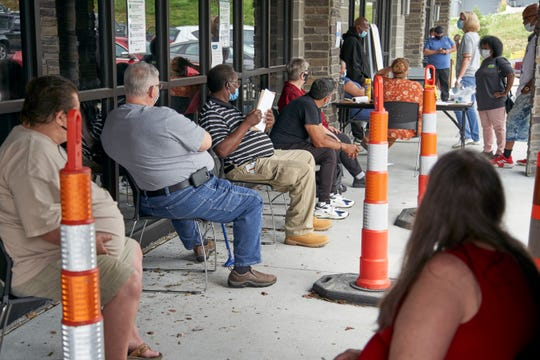 FILE - In this  July 15, 2020, file photo, job seekers exercise social distancing as they wait to be called into the Heartland Workforce Solutions office in Omaha, Neb.