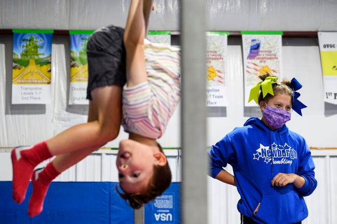 Jack Drozhinin, 6, does bar flips as Instructor Vanessa Stinnett, 18, watches other campers play during the gymnastics and tumbling summer camp held at Newburgh Tumbling in Newburgh, Ind., Wednesday morning, July 29, 2020. After being closed for over two months due to the COVID-19 pandemic, the gym began welcoming back children in late May with detailed social distancing and cleaning plans in place.