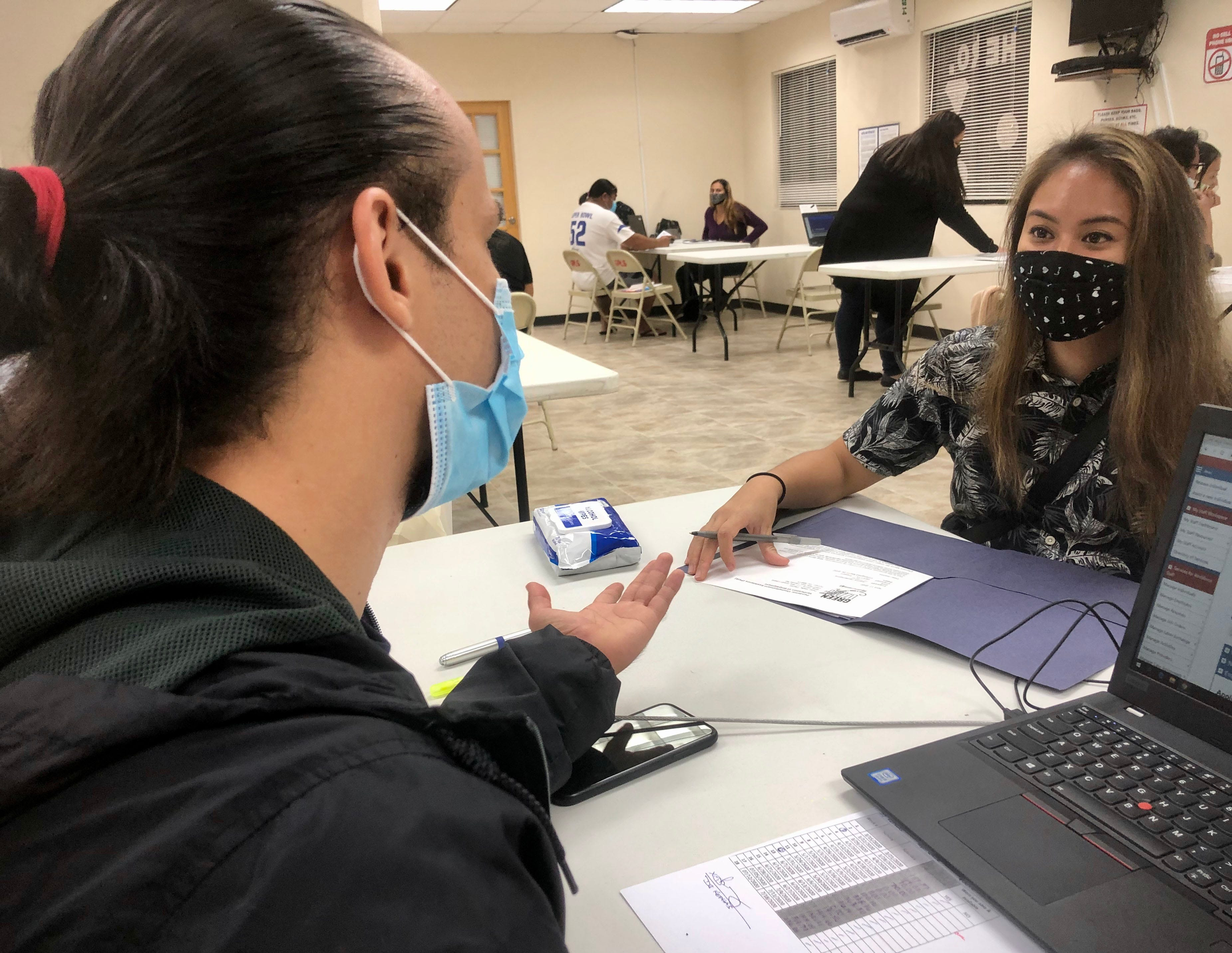In this July 28, 2020, Guam Department of Labor's customer service representative Keith Surber, left, assists applicant Joanna Opolentisima, right, with outstanding issues on her Pandemic Unemployment Assistance claim at the Hagåtña Public Library.