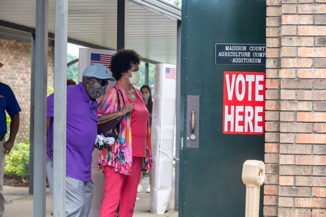 Voters wait their turn before entering the Madison County Election Commission to vote in Jackson, Tenn., Tuesday, July 28, 2020 while enforcing the CDC guidelines for the public's health.