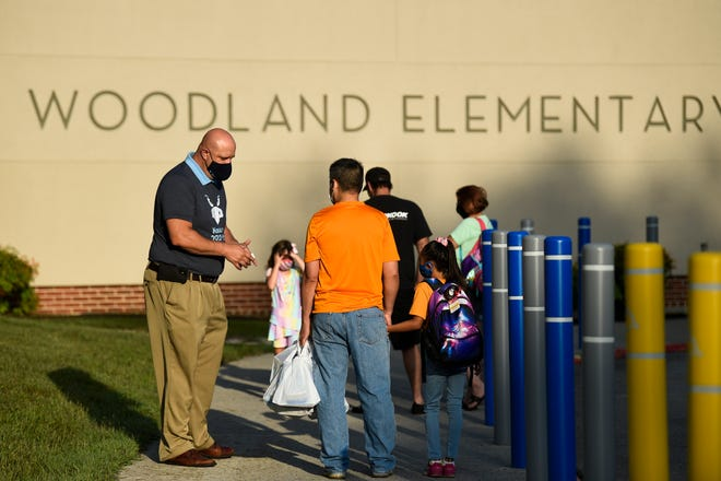 D.T. Hobby, principal of Woodland Elementary, chats with parents and students before students have their temperatures checked to prevent the spread of coronavirus, at Woodland Elementary School in Oak Ridge, Wednesday, July 29, 2020. Now, however, the school system has stopped these checks.