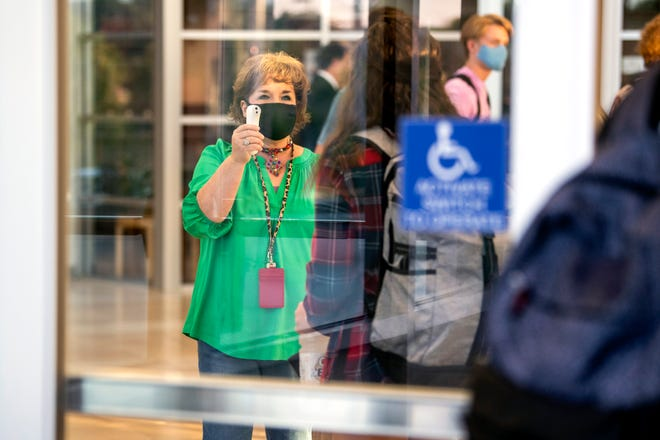 Masked Oak Ridge High students have their temperature checked as they enter the school's building for the first day of school amid COVID-19 on Wednesday, July 29, 2020.