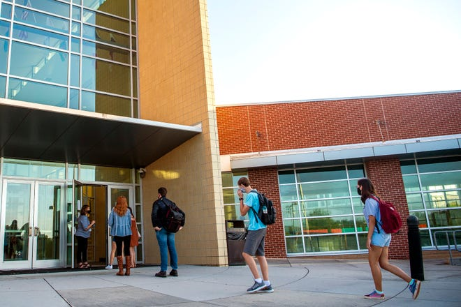 Masked students enter Oak Ridge High for the first day of school amid COVID-19 on Wednesday, July 29, 2020. All students have their temperature checked as they enter the school's building.