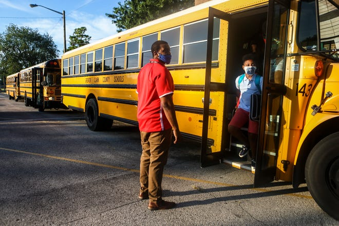 Staffer Jermane Haskins helps direct students off a bus at Parkview Middle School for the first day of classes in Jeffersonville Wednesday morning. Clark County Health Officer Dr. Eric Yazel said he and the health department were present at several schools to help the schools create a safe environment for students. July 29, 2020
