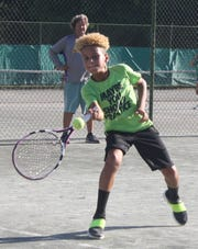 Jace Dawson, 9, of Columbus hits a forehand return at the 87th News Journal Tennis Tournament as tourney director Ron Schaub looks on