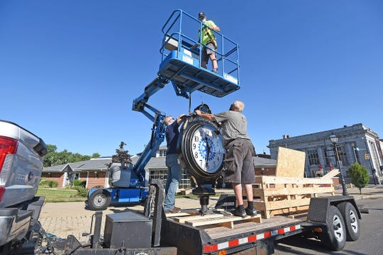 Jim Moore, Travis Porter and Todd Hultzman work to install the new clock donated by the Mansfield Rotary Club on Wednesday morning. Jason J. Molyet/News Journal
