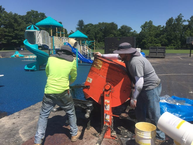Workers from Playground Equipment Services, based in Cincinnati, work to install a new blue safe surface to the newly refurbished Granville Elementary School playground July 29.