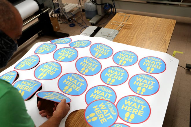 Desert Sands Unified School District digital and offset press operator Tony Fernandez works on decal stickers for social distancing inside the district administration building in La Quinta, Calif., on Wednesday, July 29, 2020. The academic year for DSUSD begins Aug. 19 with distance learning.