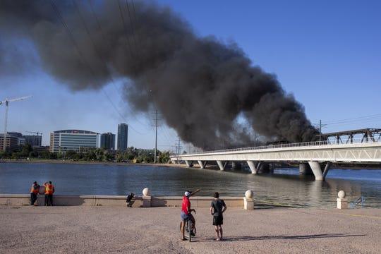 Gente observa los pilares de humo que emanan de la escena del descarrilamiento.