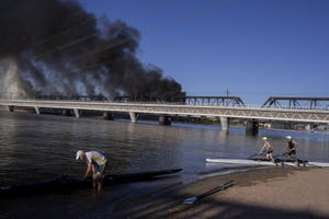Patrick Walsh, 73, (left) exits his single scull near the scene of a train derailment on July 29, 2020, at Tempe Town Lake in Tempe.