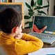 A stock image showing a boy attending a virtual math class.