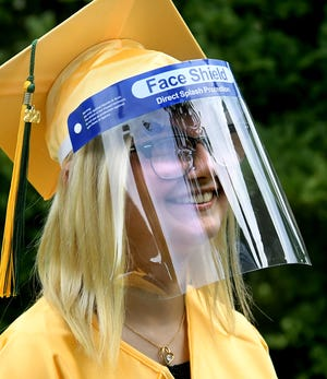 York Catholic High School senior Mikayla Ruby smiles through her face shield as students gathered outside St. Joseph Church in Springettsbury Township before limited-attendance, in-person graduation ceremonies there Tuesday, July 28, 2020. Ninety-five students graduated. Bill Kalina photo