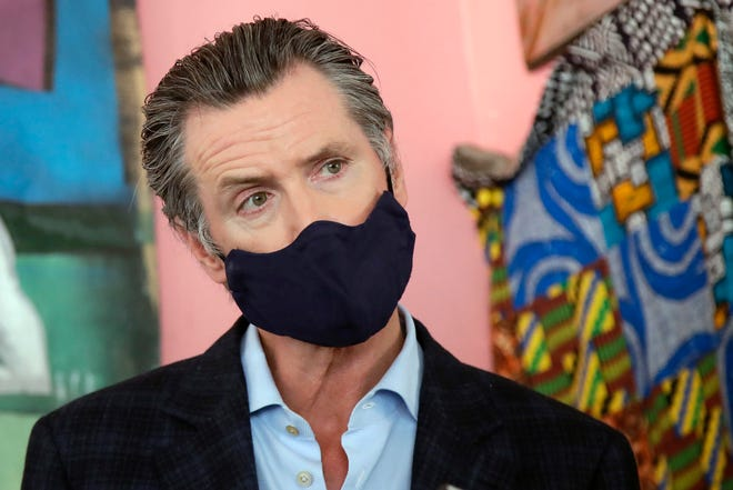 In this June 9, 2020, file photo, California Gov. Gavin Newsom wears a protective mask on his face while speaking to reporters at Miss Ollie's restaurant during the coronavirus outbreak in Oakland, Calif. According to a new poll, Americans overwhelmingly are in favor of requiring people to wear masks around other people outside their homes, reflecting fresh alarm over spiking infection rates. The poll also shows increasing disapproval of the federal government's response to the pandemic. California is among the states seeing the greatest surge in cases now.