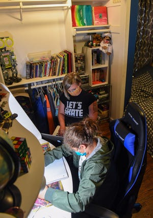TIffany Thoelke and her son, Nolan Smith, work at home on Wednesday, July 29, in Nolan's bedroom in Sioux Falls. The family has opted for Nolan to attend the Sioux Falls School District's virtual academy this school year because of the coronavirus pandemic.