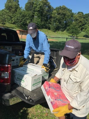 Staunton Kiwanians Dan Bonner and Rick Pfizenmayer unload a truck of donated food items from Martin's for the needy at Kiwanis Field in Gypsy Hill Park.