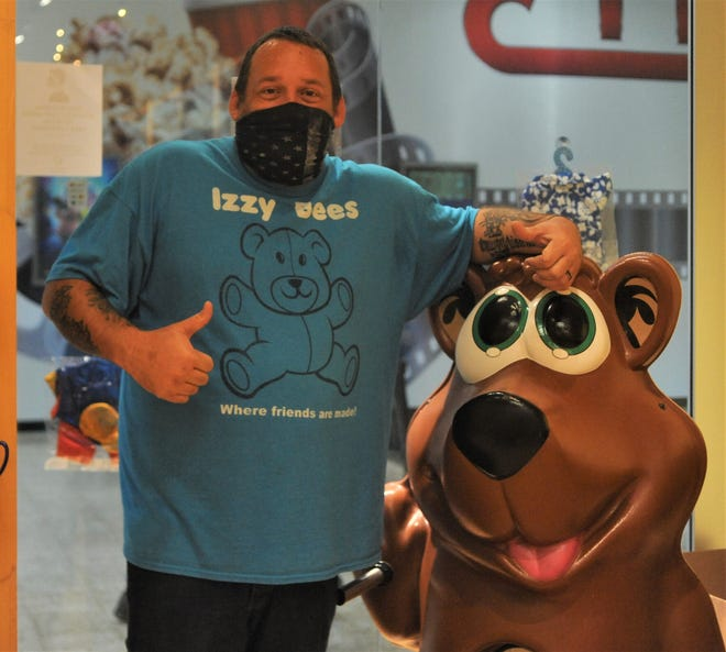 Izzy Bees owner J.D. Nicolais poses next to the stuffing bear, as Izzy Bees offers children and adults the opportunity to build their own stuffed animals. The store recently opened at the Colony Square Mall.