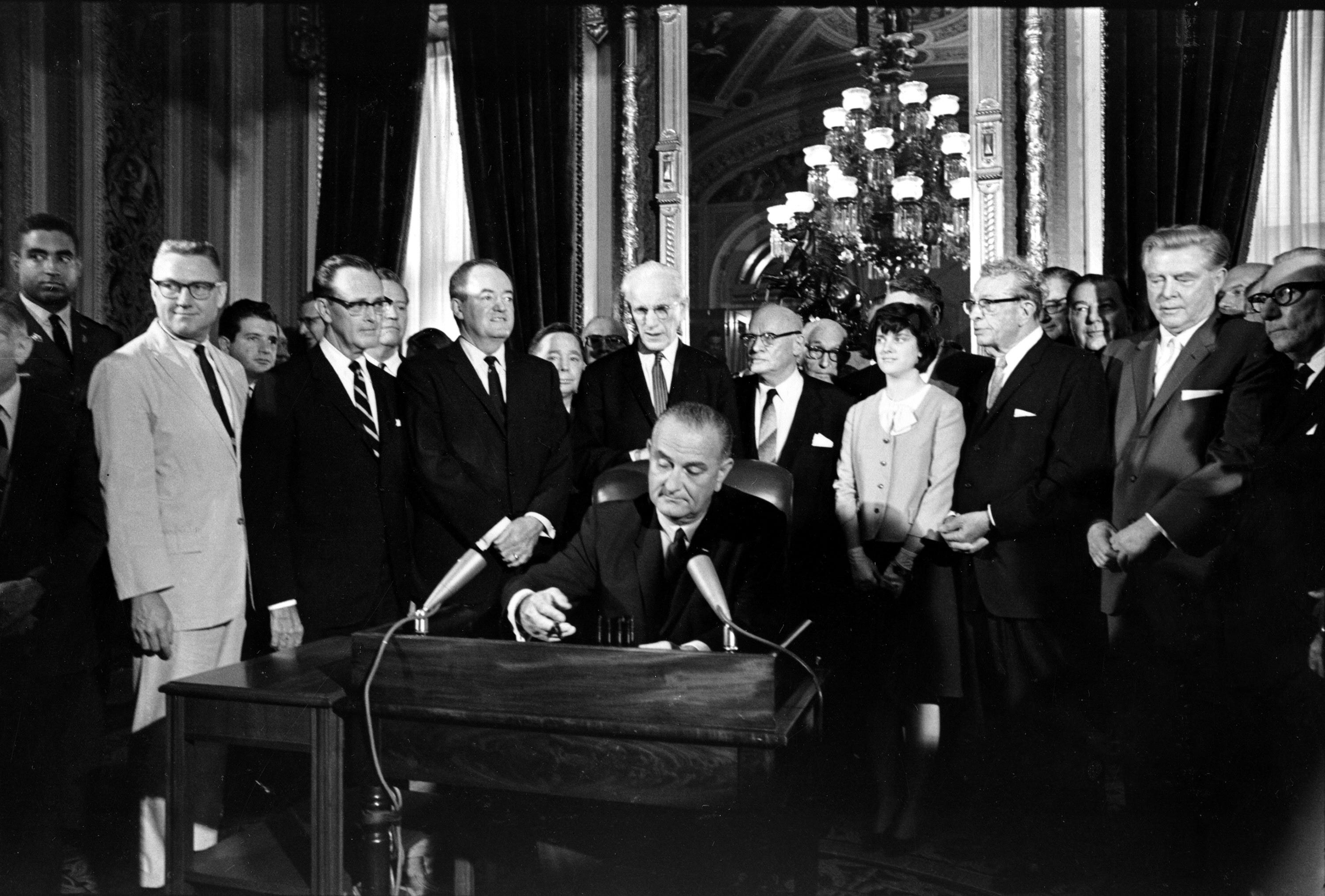 President Lyndon Johnson signs the Voting Rights Act of 1965 on Aug. 6.  Surrounding the president, from left above his right hand, Vice President Hubert Humphrey; Speaker John McCormack; Rep. Emanuel Celler, D-N.Y.; first daughter Luci Johnson; and Sen. Everett Dirkson, R-Ill.  Behind Humphrey is House Majority Leader Carl Albert of Oklahoma; and behind Celler is Sen. Carl Hayden, D-Ariz.