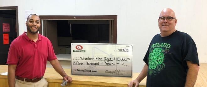 REA Director of Marketing KorDale Lornes (left) presents a $15,000 check to Love County Fire Association Chairman Bryan Rieck (right). Rieck is also Fire Chief at Lake Murray Village Volunteer Fire Department.