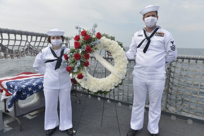Electrician's Mate 2nd Class Ashley Newman (left) and Mineman 1st Class Justin Crabtree prepare to set the wreath out to sea to commemorate the 75th anniversary of the USS Indianapolis sinking near the end of World War II. [U.S. Navy/Petty Officer 3rd Class Bea Vang]