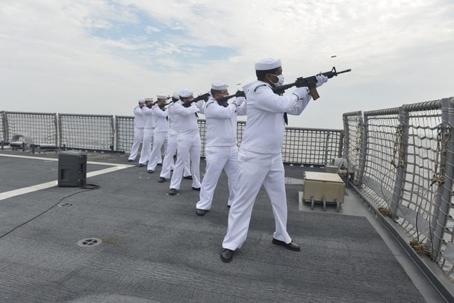 A ceremonial rifle detail fires a salute during a memorial wreath-laying ceremony at sea aboard the Mayport-based USS Indianapolis. The memorial  commemorated the 75th anniversary of the USS Indianapolis near the end of World War II. [U.S. Navy/Petty Officer 3rd Class Bea Vang]