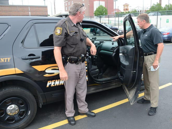 Lt. Aaron Wiersma, left, and Calhoun County Sheriff Steve Hinkley with one of the cars equipped with heating system to kill coronavirus.  Trace Christenson/The Enquirer