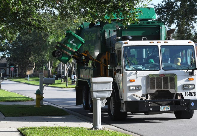 A Waste Management truck picks up trash in the Viera area.