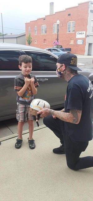 Brenton Potter of the Tattoo Factory shows Bentley Stamper his newly decorated seizure helmet earlier this month.