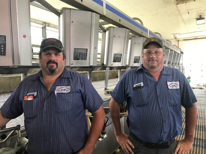 Brian Jones, left, and Steve Jones stand in their cow milking parlor on July 23, 2020.