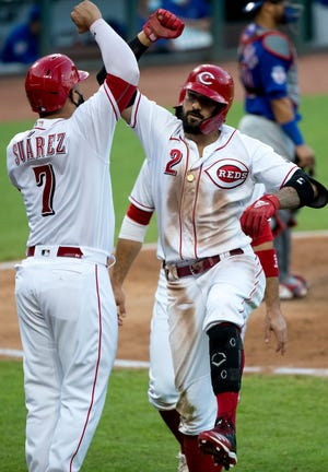 Cincinnati Reds right fielder Nicholas Castellanos (2) celebrates with Cincinnati Reds third baseman Eugenio Suarez (7) after hitting a grand slam in the fifth inning of the MLB game between the Cincinnati Reds and Chicago Cubs at Great American Ball Park in Cincinnati on Wednesday, July 29, 2020.