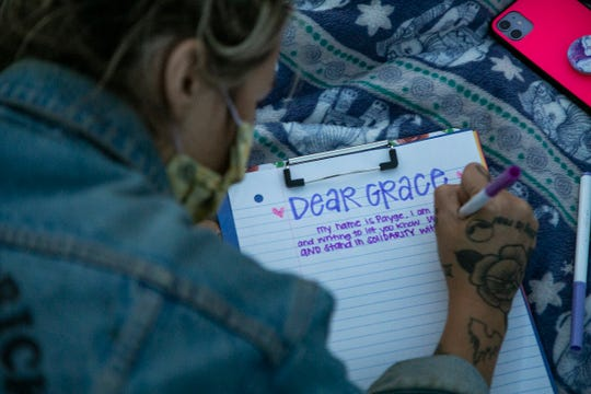 """Payge Deron, 26, of Livonia writes a letter of solidarity to """"Grace"""" on Wednesday during an overnight protest to free the Black teen."""