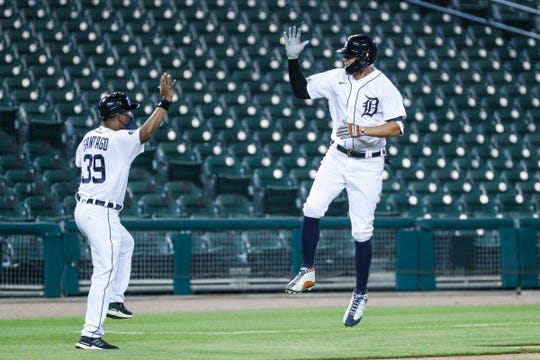 Tigers center fielder JaCoby Jones air-high-fives third base coach Ramon Santiago after hitting a home run against the Royals during the seventh inning of the Tigers' 5-4 win at Comerica Park on Wednesday, July 29, 2020.