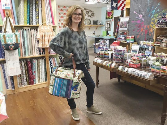 Connie Buick, owner of Lake Erie Mercantile, holding one of the bags made in a sewing class at her shop in Monroe.