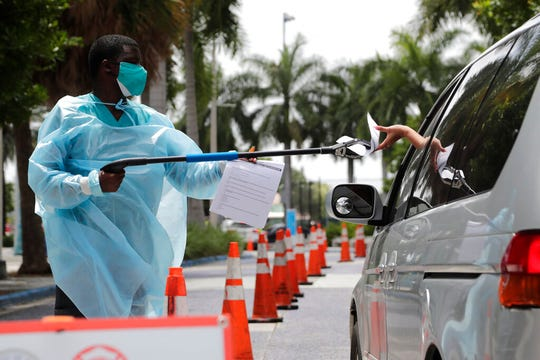 Healthcare worker Dante Hills, left, passes paperwork to a woman in a vehicle at a COVID-19 testing site outside of Marlins Park, Monday, July 27, 2020, in Miami.
