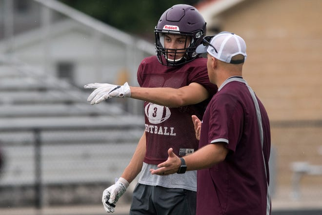 Mt. Vernon's Trevor Frisby goes over a play with head coach Luke Messmer during practice in Mt. Vernon, Ind., Wednesday evening, July 29, 2020.