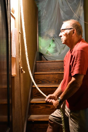 Maury Gnepper rings the bell in the bell tower stairwell at St. John's Lutheran Church on July 26. Every Sunday at 4:25 p.m. and every Wednesday at noon, Gnepper rings the 2,510-pound bell for five minutes.