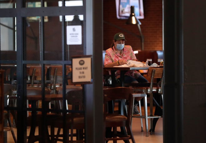 A customer looks over the menu while wearing a mask at 1919 Kitchen & Tap inside Lambeau Field in Green Bay.
