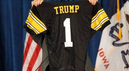 Iowa tight end Peter Pekar holds up a personalized jersey prior to the appearance of Republican presidential candidate Donald Trump at the University of Iowa Field House in Iowa City on Tuesday, Jan. 26, 2016.