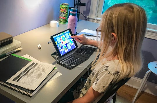 Bryna Totten, a fourth-grader, plays math games on her iPad at home during the first day of school at Washington Township. The district is starting the year virtually.