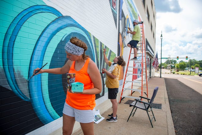 Sarah Cagle, Lisa Ingram and Jonathan Cagle paint a mural on the Southwest Tennessee Development District building Tuesday, July 28, 2020, in Jackson, Tenn. The mural, representing the culture and community of Southwest Tennessee, was sponsored by Voya Financial.