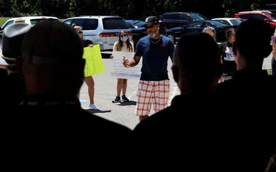 Pastor Josh Dexter, center, from City of Life Church in Lancaster, addresses Fairfield County Sheriff's Office deputies Wednesday, July 29, during an event led by Community Walking With Christ. The event was meant to show community support for the county's law enforcement officers.