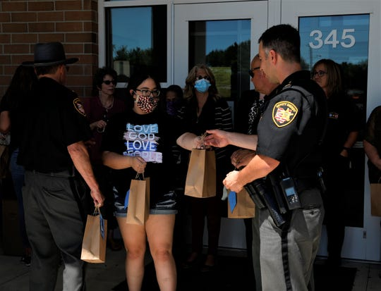 Sgt. Jesse Hendershot, right, accepts a gift bag during an event led by Community Walking With Christ in support of Fairfield County's law enforcement agencies Wednesday, July 29.