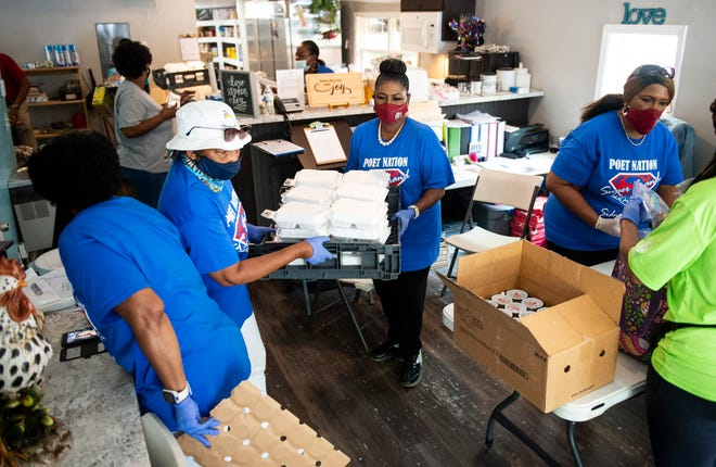 Cubie Rae Hayes, middle, helps carry meals at Mercy House in Montgomery, Ala., on Thursday, July 30, 2020.
